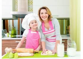 幸福微笑的母女俩在厨房一起做馅饼的肖像_11177206