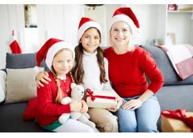 幸福的一家人坐在沙发上打开圣诞礼物_11262684