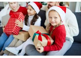 幸福的一家人坐在沙发上打开圣诞礼物_11262762