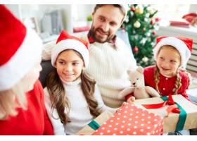 幸福的一家人坐在沙发上打开圣诞礼物_11262771