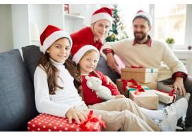 幸福的一家人拿着圣诞礼物坐在沙发上_11262708
