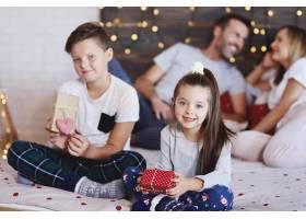 幸福的兄弟姐妹带着圣诞礼物的肖像_11757118