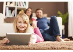 微笑的小女孩在平板上玩耍躺在地毯上_11100987