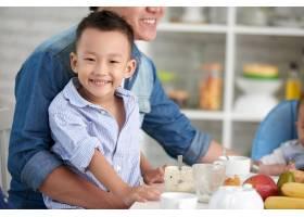 微笑的小男孩与家人共进早餐_5577378