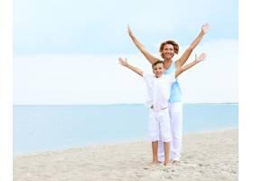 幸福的微笑的母子站在海滩上举起双手_11182562