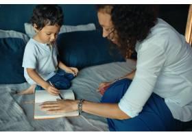 幸福美丽的年轻拉丁妇女和她可爱的小儿子坐_11554392