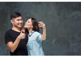 微笑的韩国夫妇在灰色工作室背景上自拍的肖_10129200