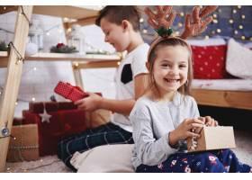 快乐女孩打开圣诞礼物的肖像_11757008