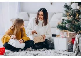 母亲和女儿在圣诞树下打包礼物_12177332