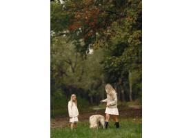 母亲和女儿在玩狗秋天公园的一家人宠物_11190954