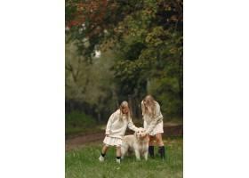 母亲和女儿在玩狗秋天公园的一家人宠物_11190962
