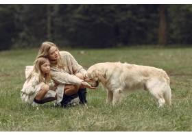 母亲和女儿在玩狗秋天公园的一家人宠物_11190994