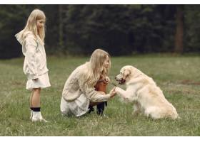 母亲和女儿在玩狗秋天公园的一家人宠物_11190998