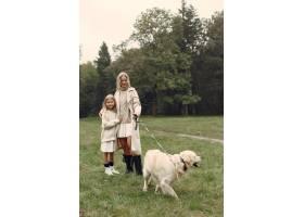 母亲和女儿在玩狗秋天公园的一家人宠物_11191030