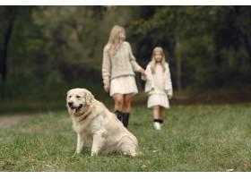 母亲和女儿在玩狗秋天公园的一家人宠物_11191069