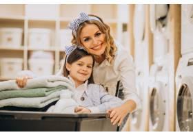 母亲和女儿在自助洗衣店洗衣服_6636943