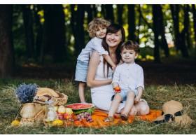 母亲和她的儿子们在森林里野餐_10298692