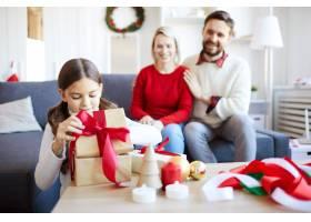 小女孩打开圣诞礼物她的父母高兴地看着她_11262544