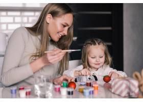 小女孩画复活节彩蛋妈妈在厨房里_8471447