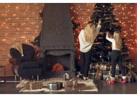 母亲带着可爱的女儿在圣诞树附近的家里_11242850