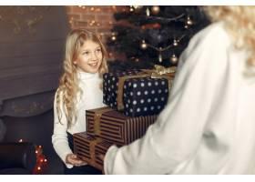 母亲带着可爱的女儿在圣诞树附近的家里_11242853