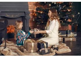 母亲带着可爱的女儿在家中靠近壁炉的地方_11243463