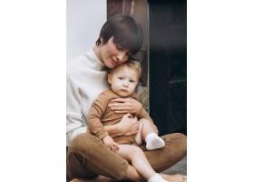 母亲和她蹒跚学步的儿子拥抱在一起_11981360