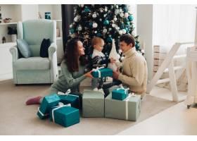 带着一个小孩子一起在圣诞树旁玩耍的欢乐的_10936790