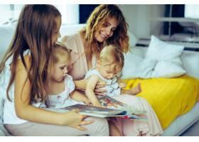 带着三个孩子的母亲在家庭式的氛围中看书_4174978