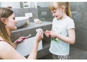 母亲在女儿的牙刷上挤牙膏_2317452