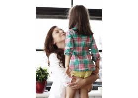 母亲在家中拥抱她的女婴_10741097