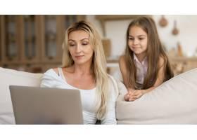 母亲在家中用笔记本电脑工作女儿在旁边看_10604675