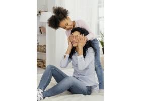 母亲在家里和她笑容可掬的女儿玩耍_13108840