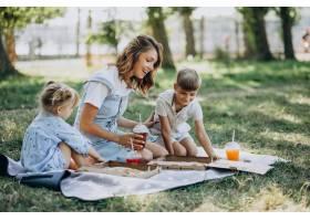母亲带着儿子和女儿在公园里吃披萨_10298454