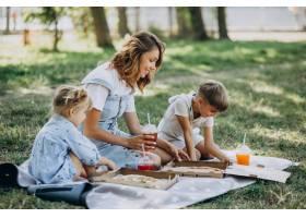 母亲带着儿子和女儿在公园里吃披萨_10298456