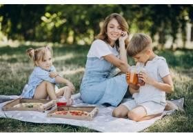 母亲带着儿子和女儿在公园里吃披萨_10298458