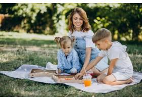 母亲带着儿子和女儿在公园里吃披萨_10298460