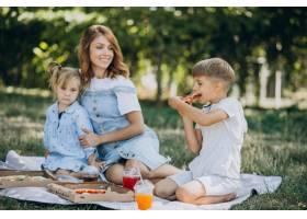 母亲带着儿子和女儿在公园里吃披萨_10298463