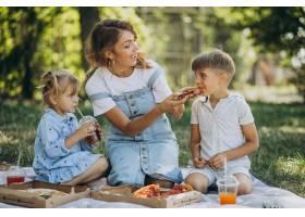 母亲带着儿子和女儿在公园里吃披萨_10298471