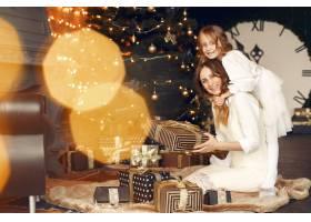 母亲带着可爱的女儿在家中靠近壁炉的地方_11243556