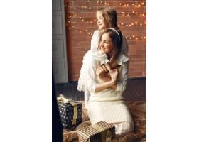 母亲带着可爱的女儿在家中靠近窗户的地方_11243617