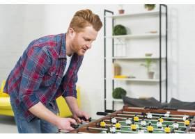年轻人在家中踢足球桌上足球比赛的特写_3894139