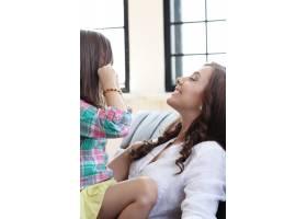 母亲带着女儿坐在沙发上_10446270