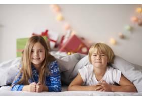 圣诞节快乐的兄弟姐妹在床上的肖像_11728012