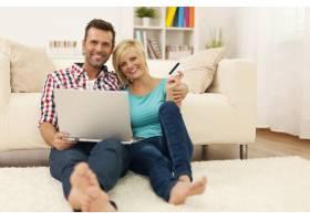 幸福恩爱的夫妇坐在地板上使用笔记本电脑_10672532