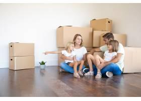 幸福的一家人坐在新家的地板上靠近纸箱_10608427