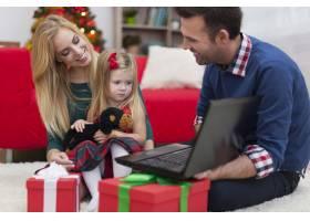 圣诞节有父母在使用笔记本电脑的小女孩_10677128