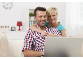 幸福的夫妇坐在客厅里使用笔记本电脑_10675031