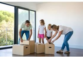 幸福的家庭带着两个孩子在新家打开箱子_10608434