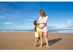 幸福的年轻妈妈和可爱的黑发女孩站在海边拥_11072651